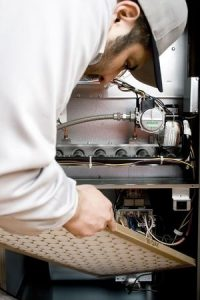 fall furnace tuneup and maintenance being done by a repairman